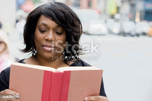 Black adult woman reading story book in downtown city, New York City