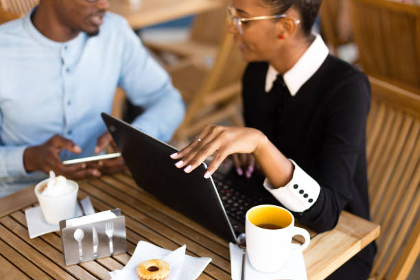 Black  African American coworkers doing digital teamwork arround a coffee cup stock photo