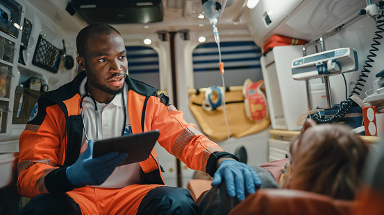 Black African American EMS Professional Paramedic Using Tablet Computer to Fill a Questionnaire for the Injured Patient on the Way to Hospital. Emergency Medical Care Assistant Works in an Ambulance.