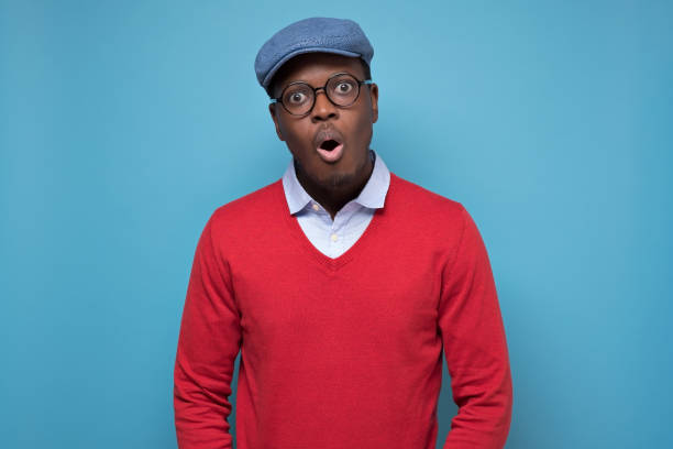 Black african american man in red sweater and blue hat looking surprised. stock photo