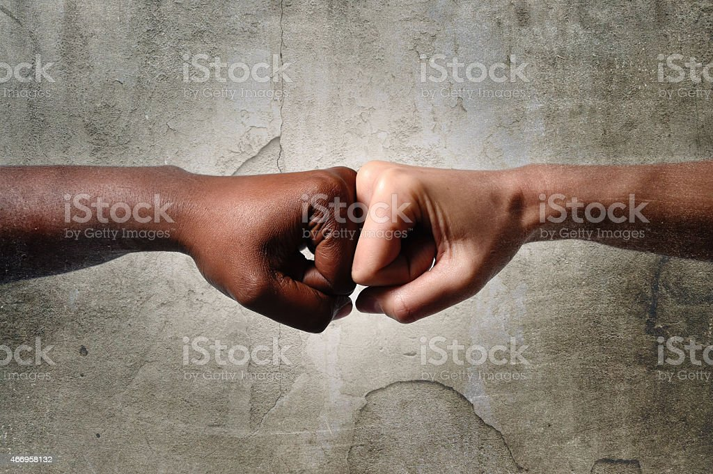 black African American race hand touching knuckles white fist stock photo
