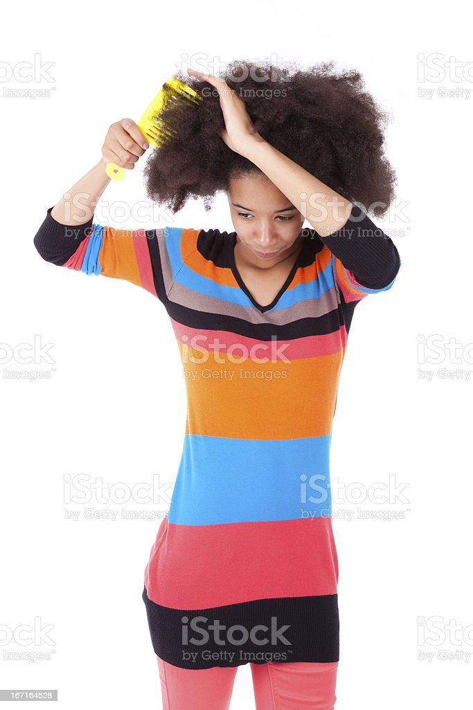 Black African American teenage girl combing her afro hair stock photo