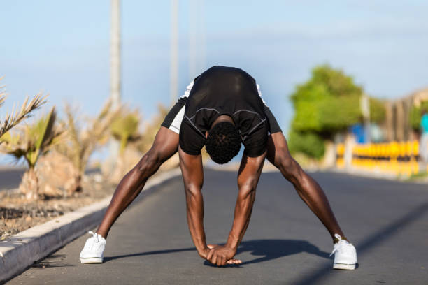 Black african american young man stretching after outdoor jogging stock photo