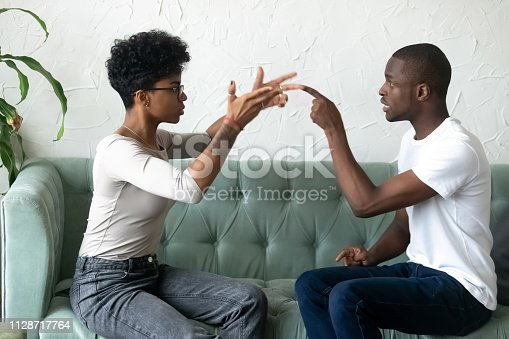 istock Black african couple quarrelling sitting on couch 1128717764