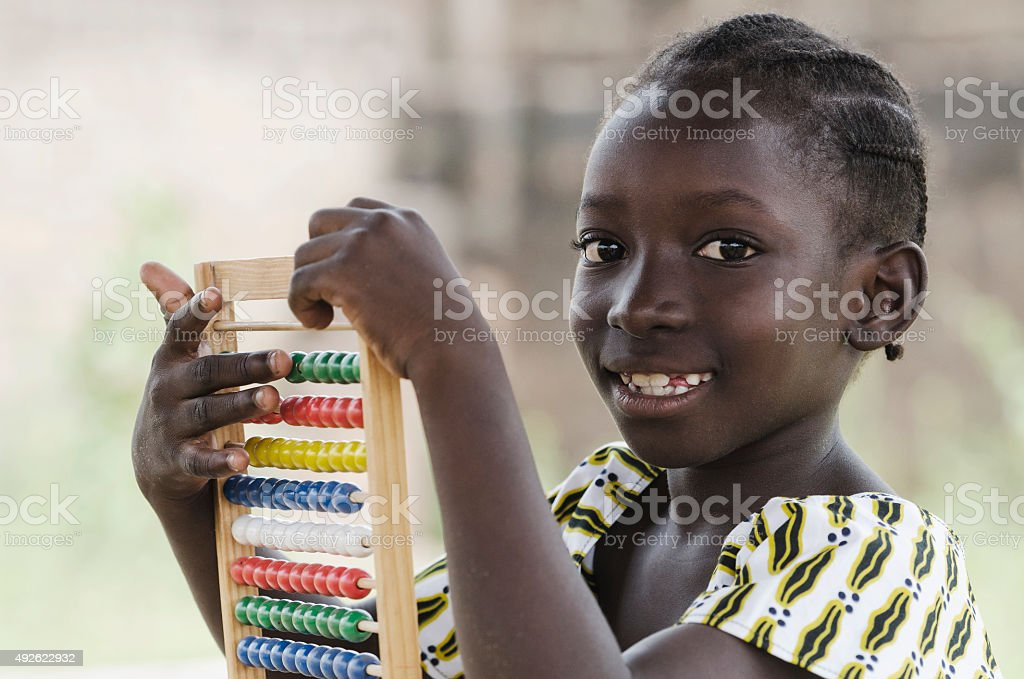 Black African Girl Playing with Abacus to Learn to Count stock photo