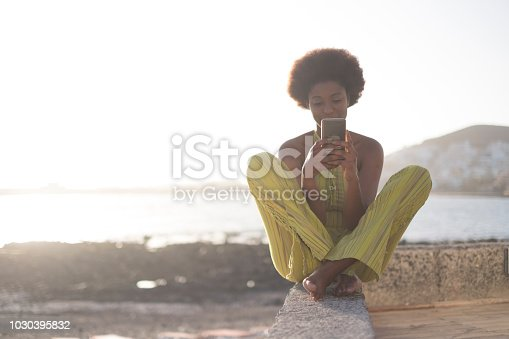 black african race young beautiful model girl 25 years old use the phone and check internet social media sitting on a wall near the ocean and water with bright sunset in background. happy leisure people activity