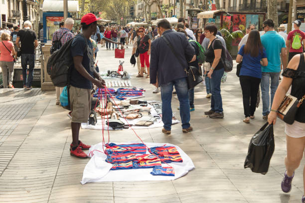 """Black african street vendors known as """"manteros"""", selling at Ramblas in Barcelona. stock photo"""