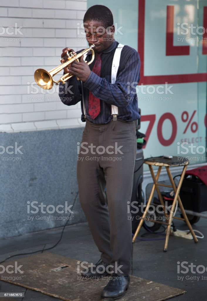Black african-american trumpet player wearing a blue shirt and red tie with white suspenders playing jazz music outside as a busker stock photo