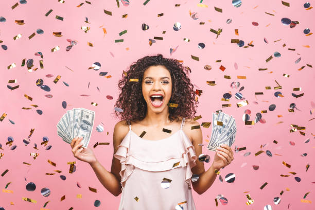 Black afro american girl won money. Happy young woman holding dollar currency satisfied isolated over pink background with confetti. Black afro american girl won money. Happy young woman holding dollar currency satisfied isolated over pink background with confetti. lottery stock pictures, royalty-free photos & images