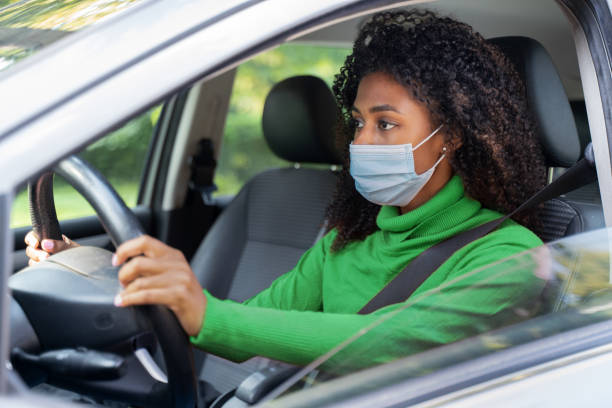 Black afro woman driving and wearing face mask stock photo