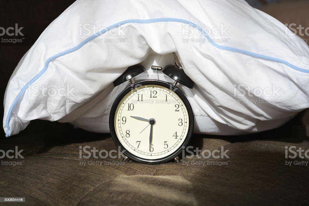 Black despertador coberto por um travesseiro branco - foto de acervo