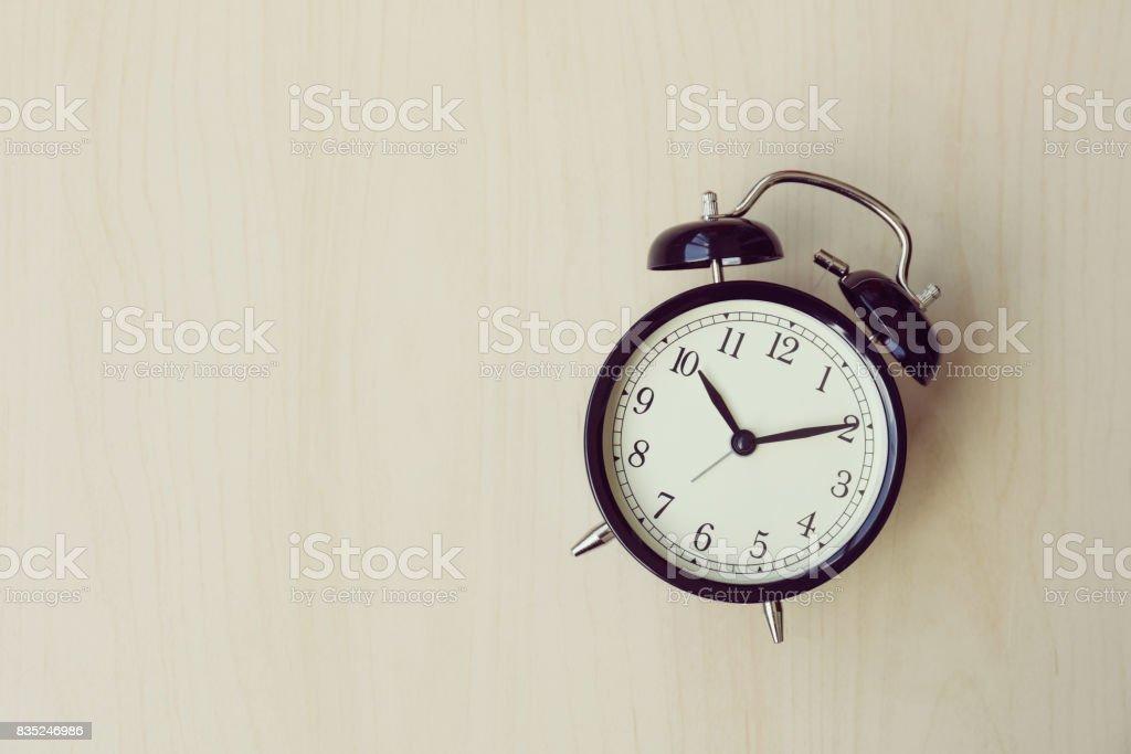 Black alarm clock on a wood background stock photo