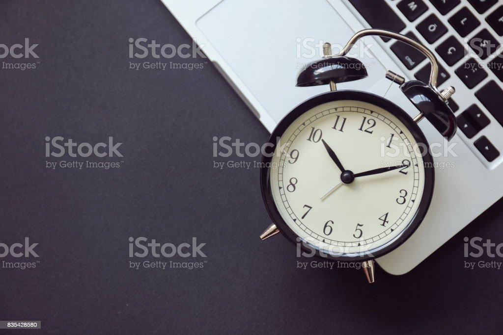 Black alarm clock on laptop
