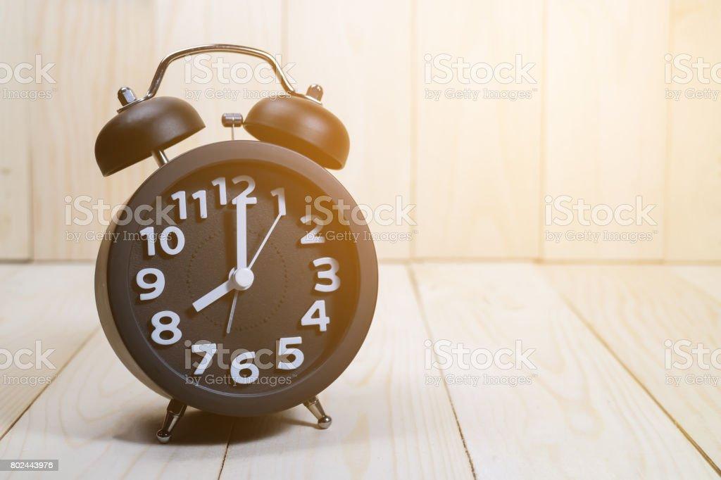 Black alarm clock  on wood background / vintage tone stock photo