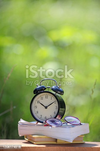 923430302 istock photo Black alarm clock stacked on organize book with nature bokeh background 1206174518