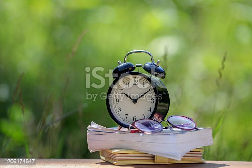 istock Black alarm clock stacked on organize book with nature bokeh background 1206174647