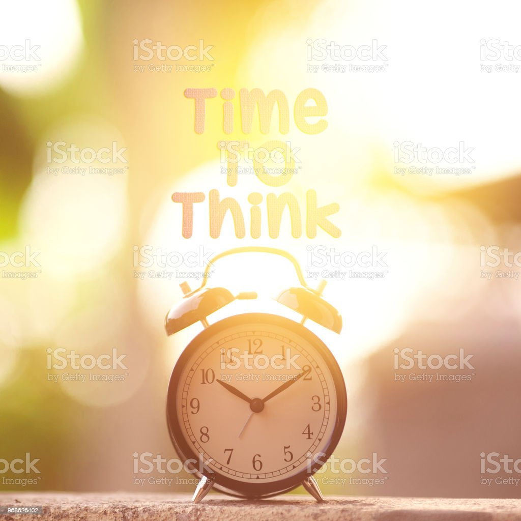Black alarm clock with \'Time to Think\' word. Concept of time