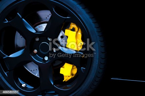 Closeup black sports car alloy wheel with yellow carbon ceramic brake, full frame horizontal composition with copy space