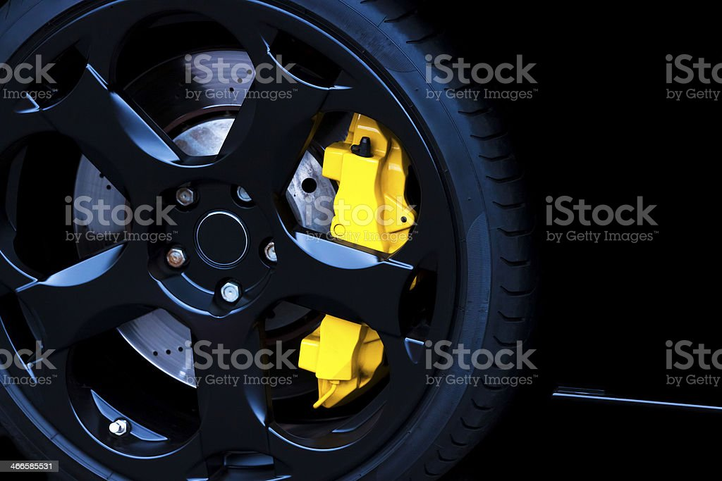 Black alloy wheel with yellow carbon ceramic brake, copy space stock photo