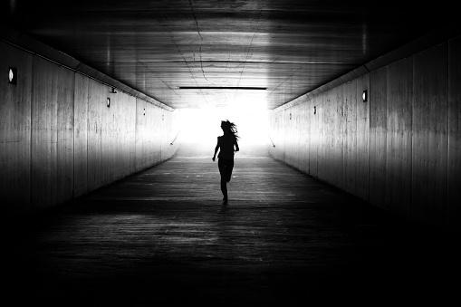 Black amd white image of girl running towards the light