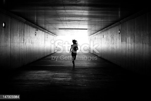Black and white conceptual image. Its a silhouette of a girl is running out of the tunnel towards the light at the end. She is determined to get out of darkness into the light. There is hope and determination.