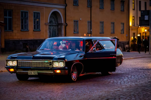 Black American car with greasers cruising at a city street at night playing loud music. stock photo