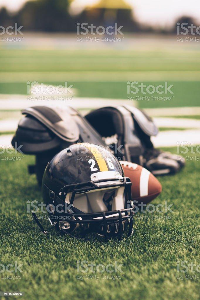 Black American Football Helmet on Playing Field stock photo