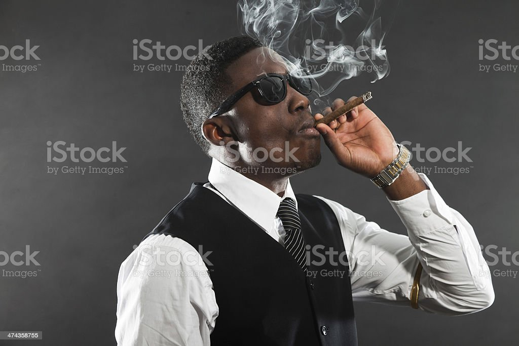 Black american mafia gangster man in suit smoking cigar. stock photo