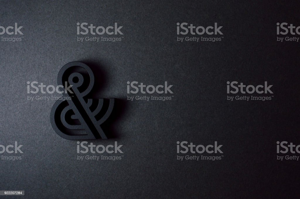 black ampersand with parallel lines on black background stock photo