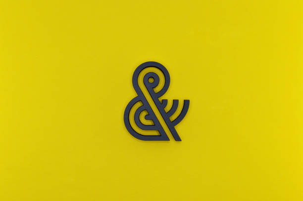 black ampersand with parallel lines on yellow background - ampersand stock pictures, royalty-free photos & images