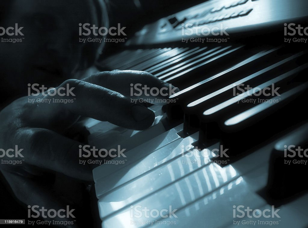 Black and blue close-up piano with hand royalty-free stock photo