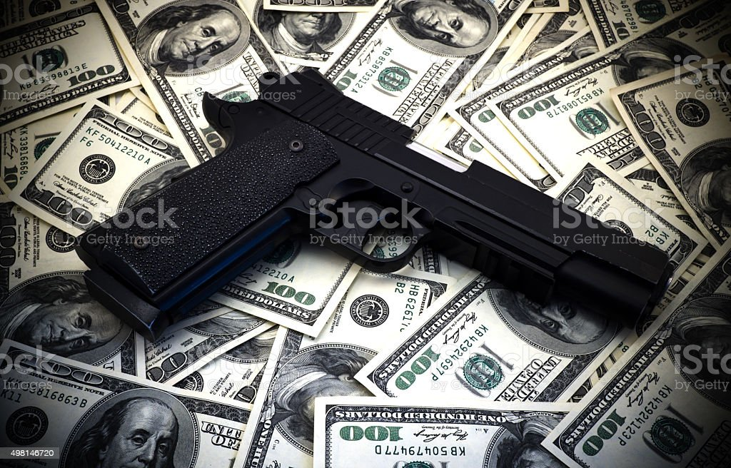 Black and chrome gun pistol and money dollars background stock photo