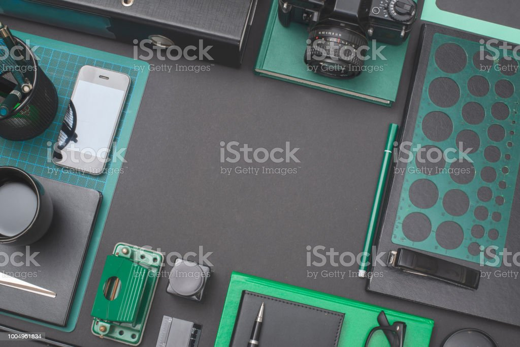 Green items on black office desk background with copy space in the...