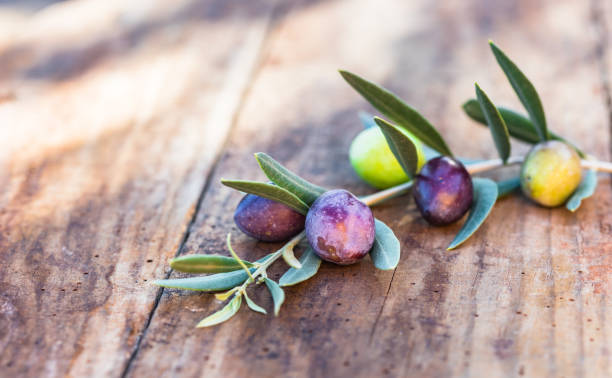 Black and green olives on wooden table stock photo