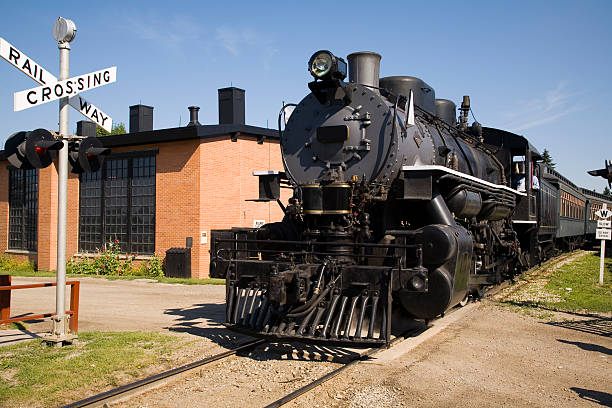A black and large steam train going through a crossing  stock photo