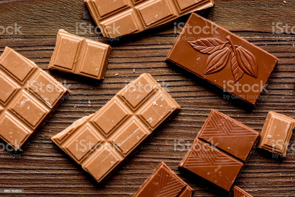 black and milk chocolate pieces wooden table background top view royalty-free stock photo