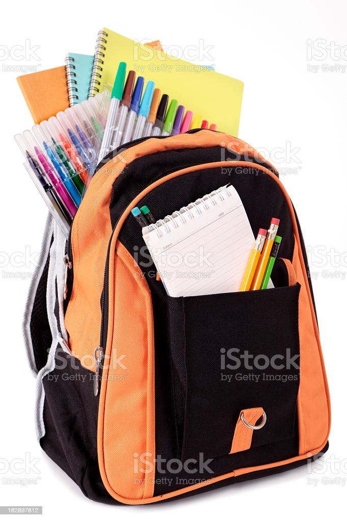 Black and orange backpack filled with school supplies stock photo