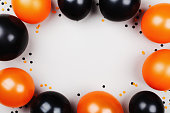 Black and orange balloons and confetti frame for Halloween card or invitation. Flat lay.