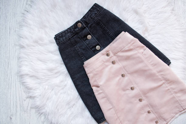 black and pink denim skirts with buttons. fashionable concept, on white fur background - spódnica zdjęcia i obrazy z banku zdjęć