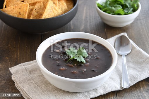 Healthy, hearty bowl of black bean and pinto bean soup shown with tortilla chips and cilantro