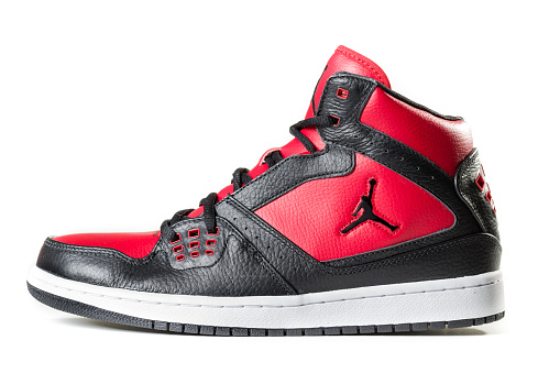New York, USA - November 22, 2012: Black Air Jordan sneaker isolated on white background. Air Jordans are a brand of shoes and athletic apparel designed and produced by Nike for the now-retired basketball player Michael Jordan.