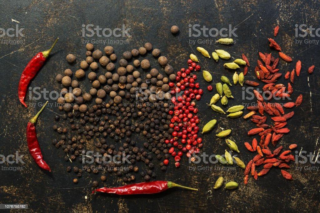 黒と赤ピーマン、チリのコショウ、カルダモンと室伏ベリー暗い背景に。様々 なスパイス。上からの眺め。 ストックフォト