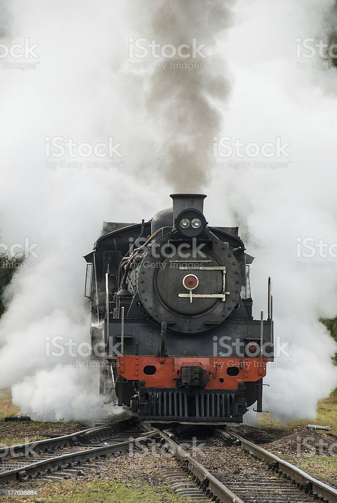 Black and red steam engine train roaring down the tracks stock photo