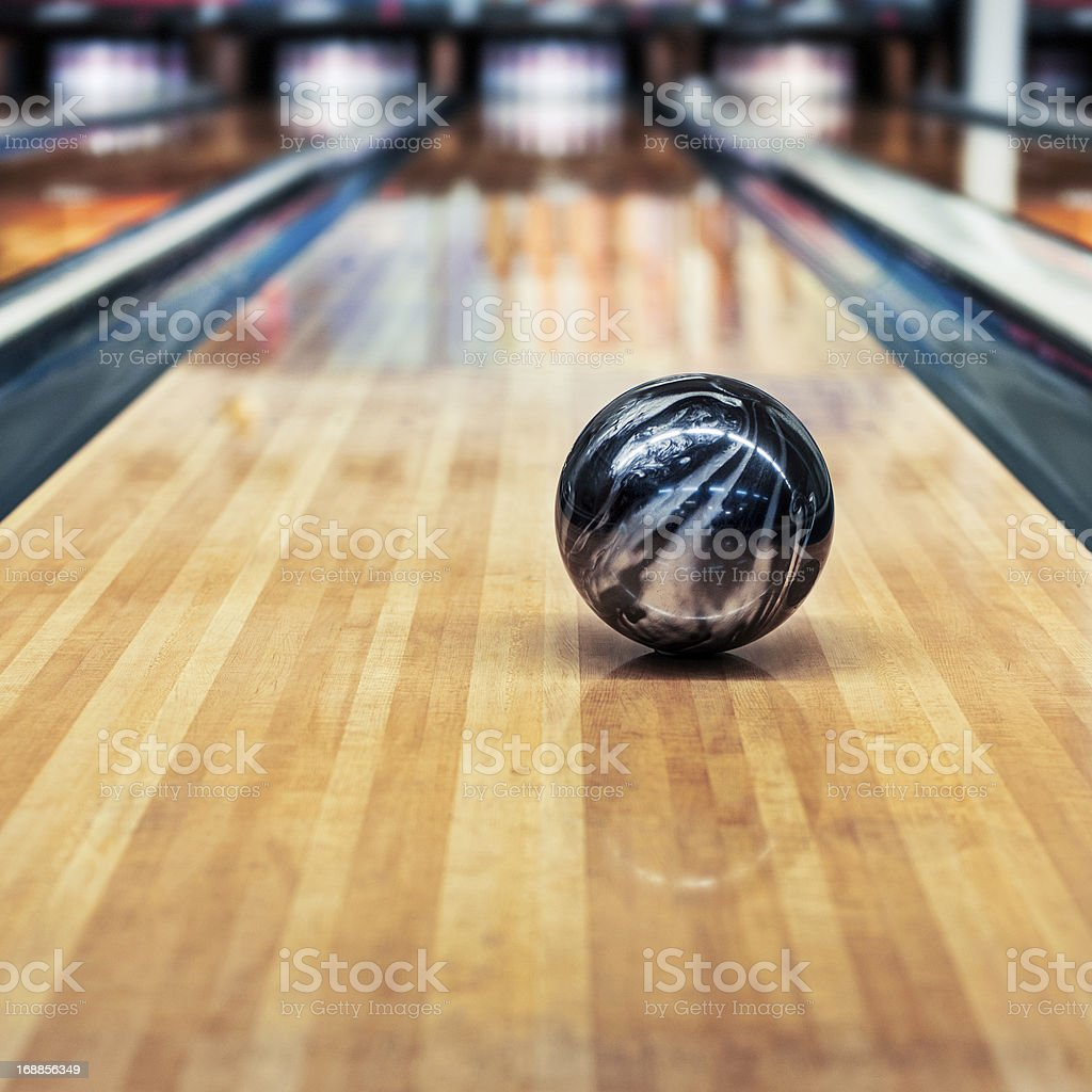 A black and silver bowling ball rolling down the lane stock photo