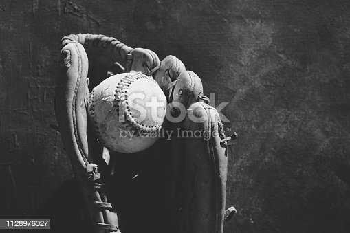 Baseball graphic flat lay in black and white with copy space.  Shows ball and glove close-up with antique style.