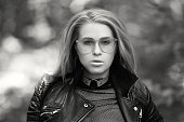 attractive fashion model in nature wearing leather jacket and eyeglasses.