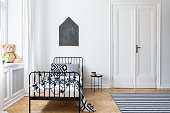 Black and white bed in teenager's bedroom interior with plush toy and poster on the wall. Real photo