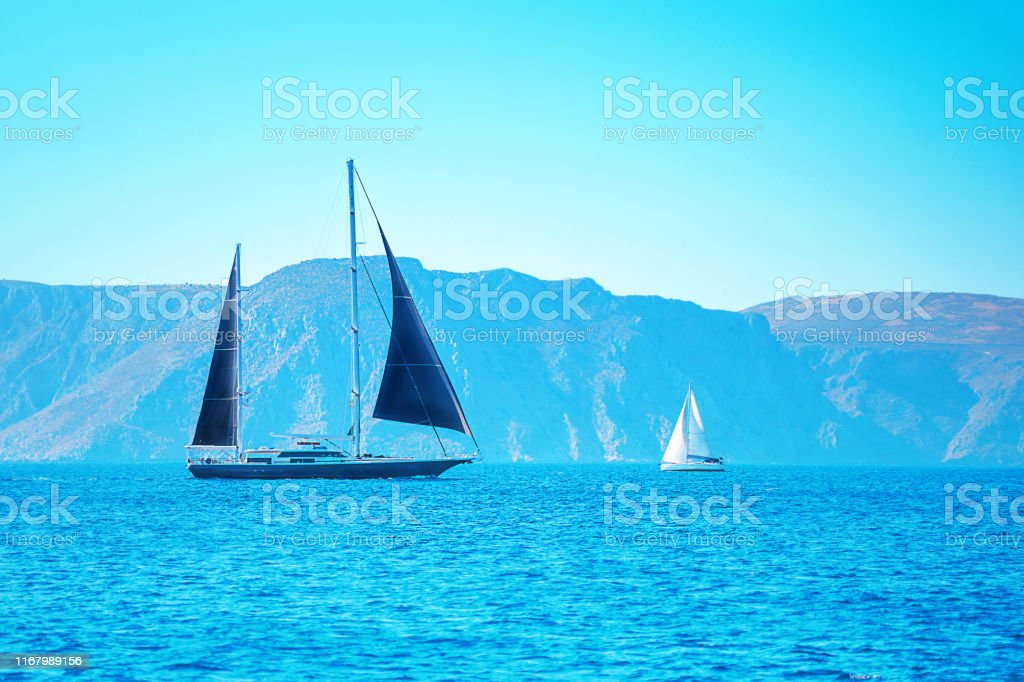 Black and white boat sailing in the open blue sea in Greece....