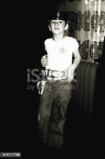 vintage photo from the seventies of a boy  playing the cowboy at home.