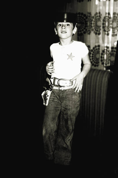 Black and white boy playing the cowboy vintage photo from the seventies of a boy  playing the cowboy at home. 20th century style stock pictures, royalty-free photos & images
